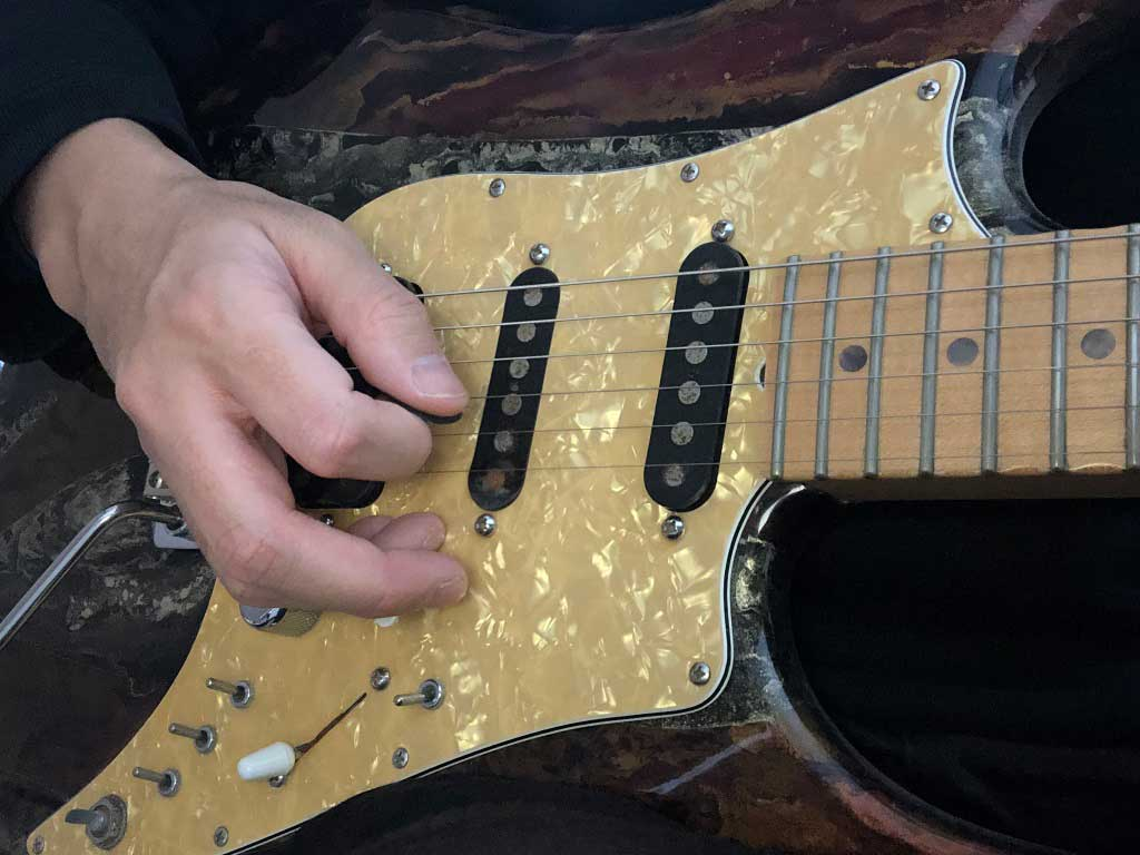 薬指と小指をピックガードに置いているフォーム